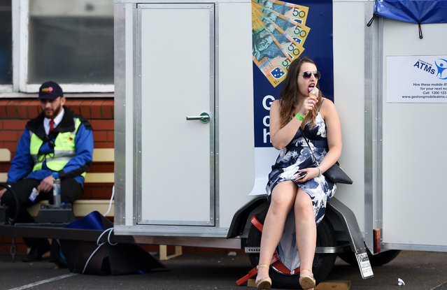 A race goer eats an ice cream at an atm after the Geelong Cup on Geelong Cup day at Geelong Racecourse in Melbourne, Wednesday, October 19, 2016. (Photo by Tracey Nearmy/AAP Image)
