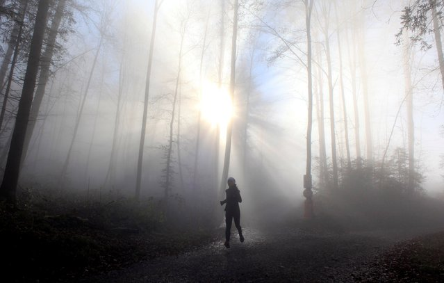 A woman joggs during foggy weather in a forest, in Zurich, Switzerland on November 26, 2020. (Photo by Arnd Wiegmann/Reuters)