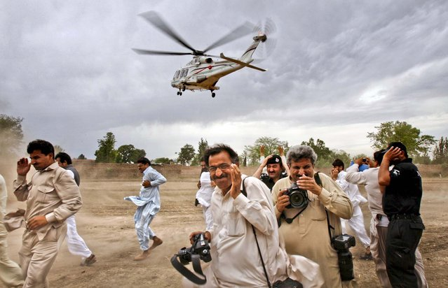 People rush for cover as Pakistan's former Prime Minister Nawaz Sharif leaves in a helicopter after addressing an election rally near Peshawar, Pakistan, on May 7, 2013.  (Photo by Mohammad Sajjad/Associated Press)