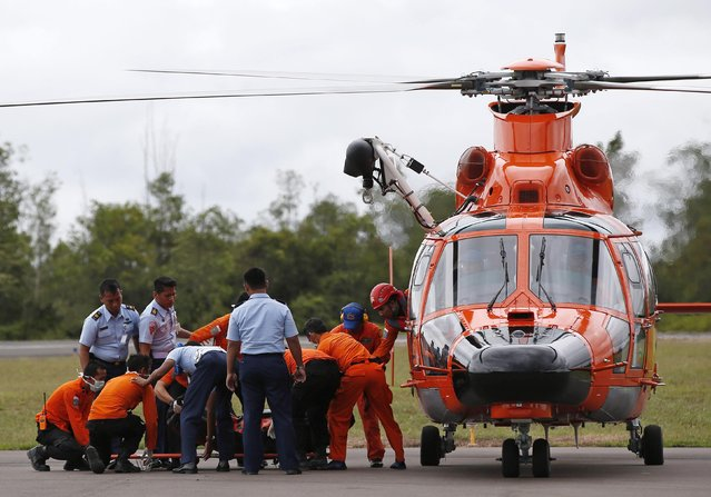 Indonesian Search and Rescue crews unload one of two bodies of AirAsia passengers recovered from the sea, at the airport in Pangkalan Bun, Central Kalimantan, December 31, 2014. (Photo by Darren Whiteside/Reuters)