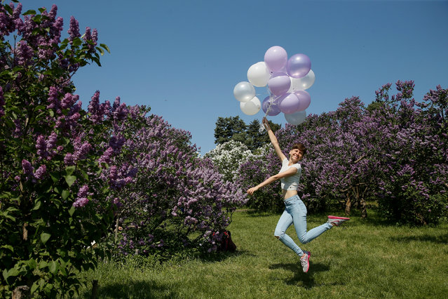 A woman jumps with balloons while she poses for a picture at a park in Kiev, Ukraine May 6, 2018. (Photo by Valentyn Ogirenko/Reuters)