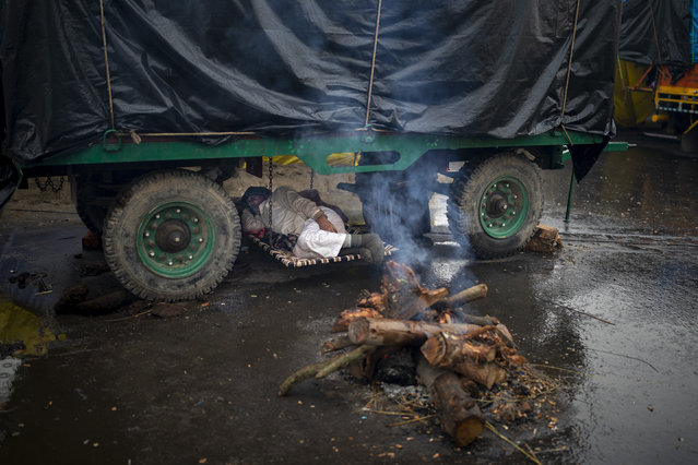 A farmer lies under the belly of a tractor trolley next to a bonfire as they block a major highway in a protest against new farm laws while it rains at the Delhi-Uttar Pradesh state border, India, Monday, January 4, 2021. (Photo by Altaf Qadri/AP Photo)