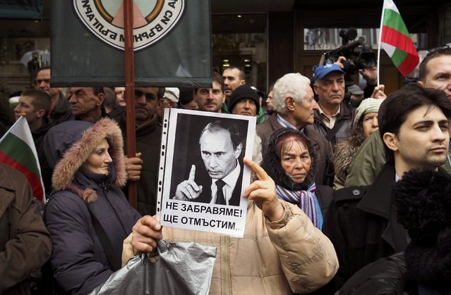 """A supporter of Bulgaria's nationalist Attack party holds a picture of Russian President Vladimir Putin during a protest supporting Russia in front of the Turkish embassy in Sofia, Bulgaria, November 26, 2015. The text reads in Bulgarian: """"We don't forget! We will revenge"""". (Photo by Pierre Marsaut/Reuters)"""