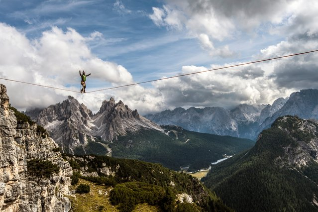 """""""Walking high in the Dolomites"""". The international high line festival at Monte Piana (2,324m) in the Italian Dolomites, above the small town of Misurina. The mountain is popular with slackliners who take advantage of its numerous buttresses, suspending thin lines between the spectacular cliffs and then walking over the gaps. Honourable mention: Travel. (Photo by James Rushforth/SIPA Contest)"""