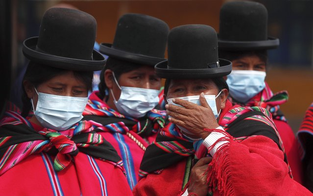 Aymara Indigenous women wearing masks amid the new coronavirus pandemic wait to enter the archaeological museum in Tiwanaku, Bolivia, Tuesday, January 12, 2021. Bolivian archaeologists are presenting the findings of a recent discovery of ancient vessels unearthed in a dig on the site once home to one of the most significant pre-Hispanic empires, the Tiwanacota. (Photo by Juan Karita/AP Photo)