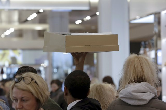 A staff member lifts a shoe box at Macy's Herald Square store during the early opening of the Black Friday sales in the Manhattan borough of New York, November 26, 2015. (Photo by Andrew Kelly/Reuters)