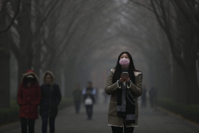 A woman wearing a mask walk in a street in a Yonghegong Lama temple compound seen shrouded in smog in Beijing, China, 30 November 2015. Beijing issued an orange alert for heavy smog 30 November, the highest level this year. Authorities in the Chinese capital warned of 'severe pollution' and advised the capital's 20 million inhabitants to stay indoors. (Photo by How Hwee Young/EPA)