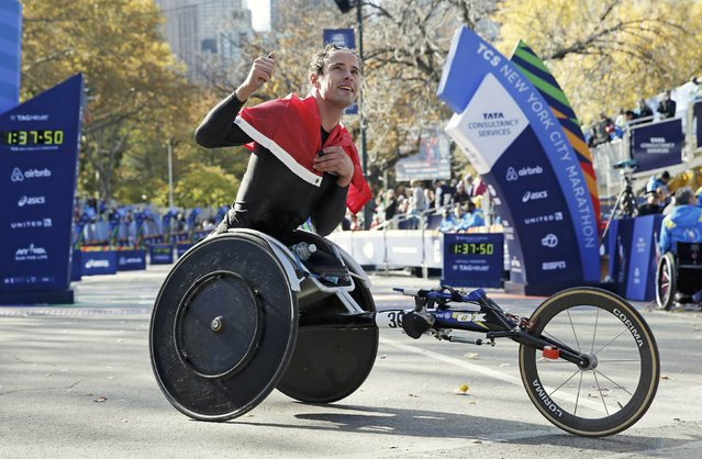 Marcel Hug of Switzerland celebrates after winning the mens wheelchair division of the 2016 New York City Marathon in Central Park in the Manhattan borough of New York City, New York, U.S. November 6, 2016. (Photo by Mike Segar/Reuters)