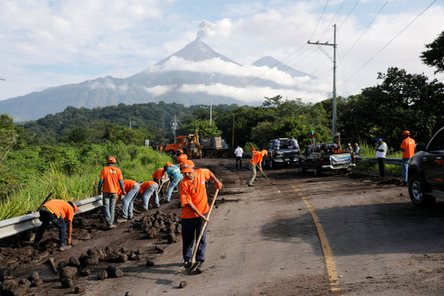 Workers clean the road after lahar flowed down from the Fuego volcano at El Rodeo in Escuintla, Guatemala June 12, 2018. (Photo by Carlos Jasso/Reuters)
