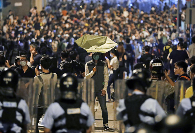 A protester holds a yellow umbrella in front of police officers after clashing as thousands of people march in a Hong Kong street, Sunday, November 6, 2016. Thousands of protesters marched in Hong Kong on Sunday, demanding that China's central government stay out of a political dispute in the southern Chinese city after Beijing indicated that it would intervene to deter pro-independence advocates. (Photo by Kin Cheung/AP Photo)