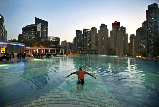 In this April 12, 2015 photo, a man dives into a hotel pool  in the Marina neighborhood of Dubai, United Arab Emirates. The Marina is one of many clusters of neck-bending skyscrapers built throughout Dubai, but its real power lies behind the gated privacy of its most luxurious towers. Owning an apartment in one of these towers means access to skyline pools, concierge services and grand apartments that cater to the region's royalty, as well as the world's wealthiest businessmen and women. (Photo by Kamran Jebreili/AP Photo)