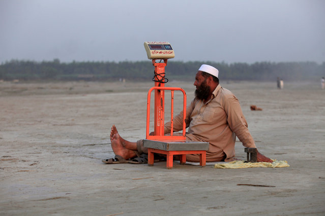A blind man sits beside his scales waiting for customers at a picnic spot on the beach of the Sardaryab river in Charsadda outside Peshawar, Pakistan October 18, 2016. (Photo by Fayaz Aziz/Reuters)