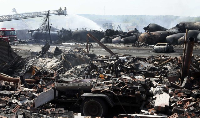 The remains of a home lie in rubble as firefighters continue working on the scene of a train derailment in Lac Megantic, Quebec, July 7, 2013.  A driverless freight train carrying tankers of petroleum products derailed at high speed and exploded into a giant fireball in the middle of the small Canadian town of Lac-Megantic early on Saturday, destroying dozens of buildings and leaving an unknown number of people feared missing. (Photo by Christinne Muschi/Reuters)