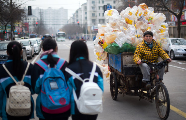 A man rides his loaded tricycle next to three schoolgirls in Shanghai on  December 11, 2015. (Photo by Johannes Eisele/AFP Photo)