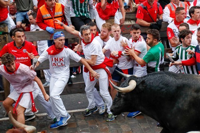 Participants run next to a Puerto de San Lorenzo's fighting bull on the first day of the San Fermin bull run festival in Pamplona, northern Spain on July 7th 2018. (Photo by Zuma/Splash News and Pictures)