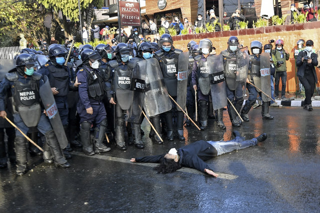A protester from the civil society lies down in front of policemen during a demonstration against the dissolution of the country's parliament in Kathmandu on January 25, 2021. (Photo by Prakash Mathema/AFP Photo)