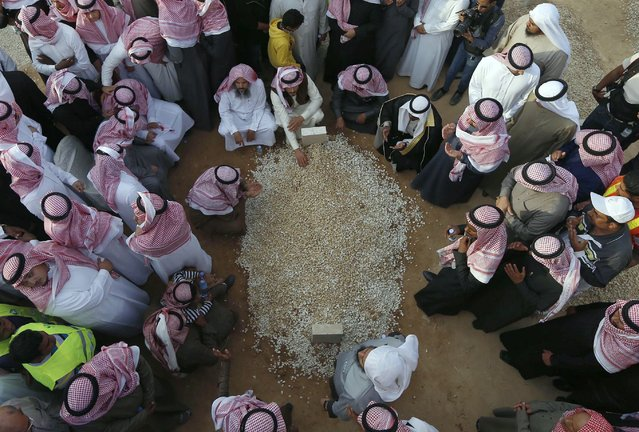 Mourners gather around the grave of Saudi King Abdullah following his burial in Riyadh January 23, 2015.  Saudi King Salman pledged on Friday to maintain existing energy and foreign policies then quickly moved to appoint younger men as his heirs, settling the succession for years to come by naming a deputy crown prince from his dynasty's next generation. (Photo by Reuters/Stringer)