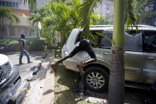 In this July 7, 2018 photo, a man looks inside a car before setting it on fire at the Royal Oasis hotel during protests over a fuel price increase in Port-au-Prince, Haiti. On Friday, the government announced that it would raise the prices of gasoline, diesel and kerosene from 38 percent to 51 percent beginning Saturday. (Photo by Dieu Nalio Chery/AP Photo)