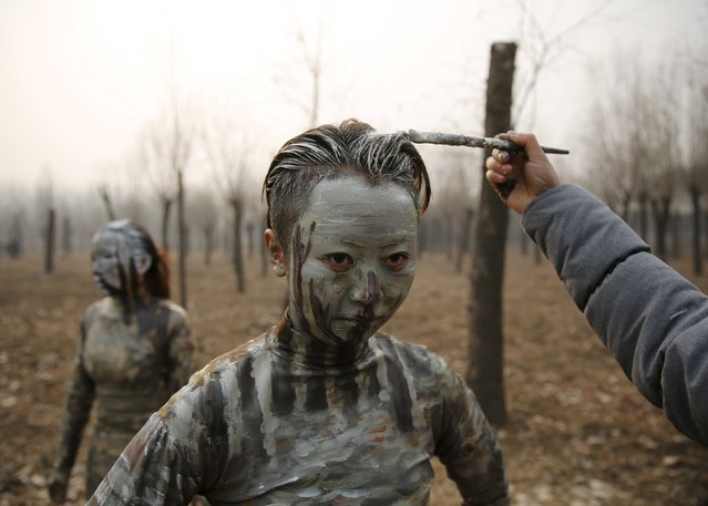 """A staff paints a model with camouflage colours to blend her in with the background for Chinese artist Liu Bolin's artwork """"Dongji"""", or Winter Solstice, on the second day after China's capital Beijing issued its second ever """"red alert"""" for air pollution, in Beijing, China, December 20, 2015. (Photo by Kim Kyung-Hoon/Reuters)"""