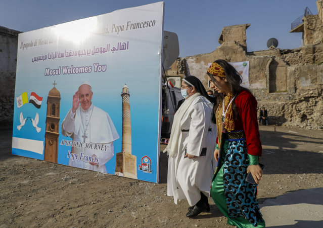 Surrounded by destroyed buildings people arrive to join Pope Francis who will pray for the victims of war at Hosh al-Bieaa Church Square, in Mosul, Iraq, once the de-facto capital of IS, Sunday, March 7, 2021. (Photo by Andrew Medichini/AP Photo)