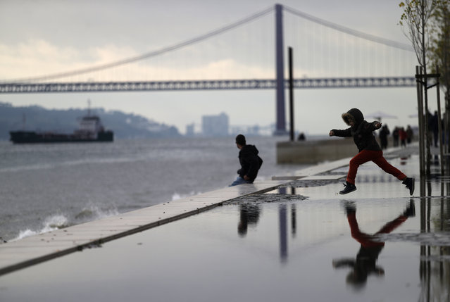 A young boy jumps over a puddle by the Tagus riverbank, in Lisbon, Sunday, January 18, 2015. At the background is the April 25th bridge, whose name was given after the Carnations revolution that restored the democracy in Portugal in April 1974. (Photo by Francisco Seco/AP Photo)