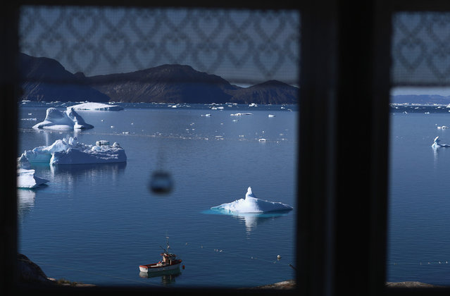 Icebergs, viewed through a kitchen window in Qeqertaq, Greenland, on July 20, 2013. (Photo by Joe Raedle/Getty Images via The Atlantic)