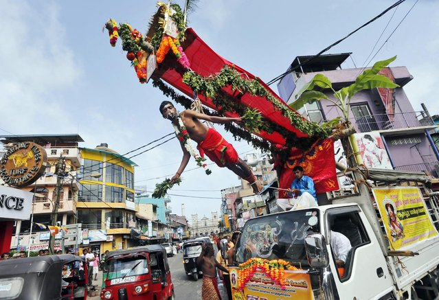 "A truck carries a Sri Lankan Hindu devotee hanging with iron hooks pierced into his back as a ritual during a Hindu temple festival in Colombo, Sri Lanka, Friday, August 9, 2013. Hindu devotees mark ""Paal Kudam"" or the festival of milk by pouring milk on the idols of their deity and seek their blessings. (Photo by Eranga Jayawardena/AP Photo)"