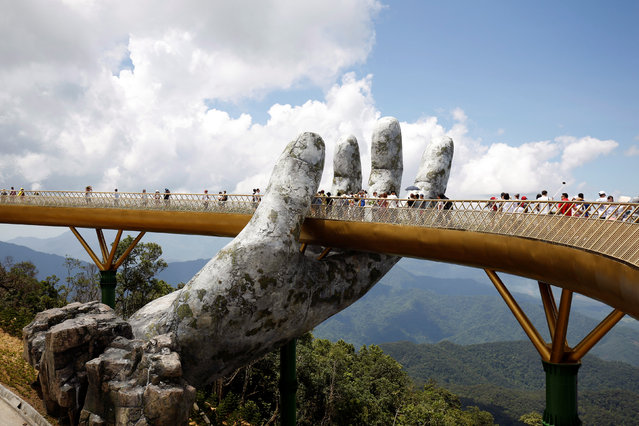 Tourists walk past giant hand structure on Gold Bridge on Ba Na hill near Danang city, Vietnam on August 1, 2018. (Photo by Reuters/Kham)
