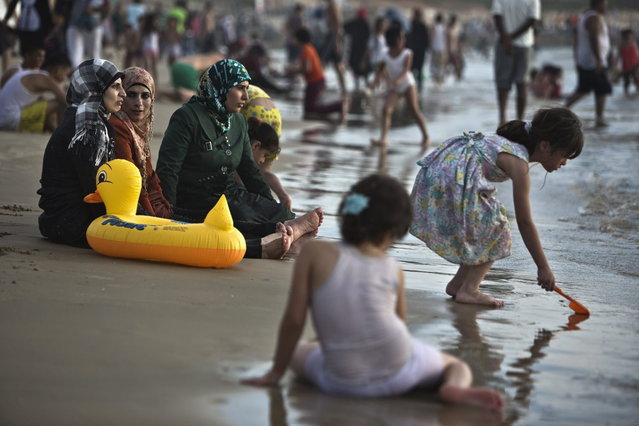 Palestinian women from Ramallah sit together at the shore of the Mediterranean sea at a beach in Tel Aviv during Eid al-Fitr, which marks the end of the holy month of Ramadan August 11, 2013. The Israeli Coordinator for Government Activities in the Territories' (COGAT) responsible for implementing Israel's civilian policy in the occupied West Bank and Gaza Strip, eased permit restrictions for thousands of Palestinians wanting to enter Israel following a security assessment, allowing many to enjoy the beaches along Israel's Mediterranean shoreline during the Eid al-Fitr holiday. (Photo by Nir Elias/Reuters)