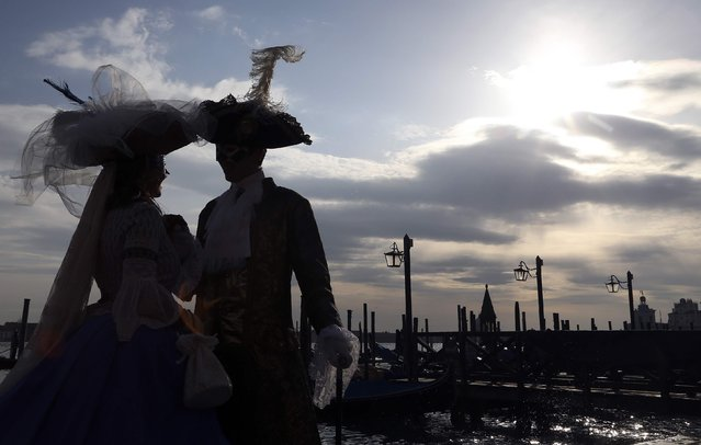 Masked revellers are silhouetted as they pose in front of St. Mark's Square during the Venice Carnival, February 7, 2015. (Photo by Stefano Rellandini/Reuters)
