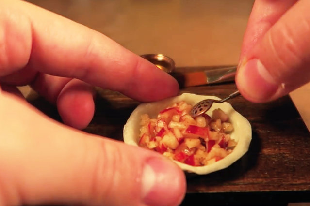 Jay fills the tiny pie crust with apples. (Photo by Jay Baron/Caters News)