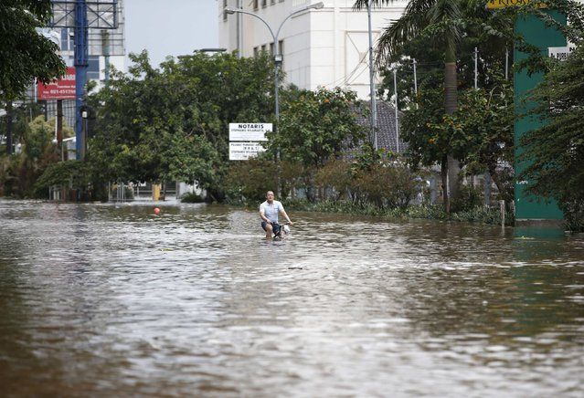 A man rides his bicycle through a flooded street after continuous heavy seasonal rains inundated many parts of Jakarta February 10, 2015. (Photo by Darren Whiteside/Reuters)
