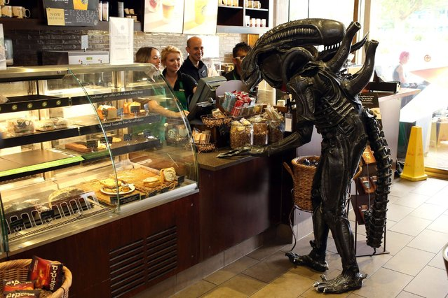 A Si-Fi enthusiast dressed as the alien from the iconic science fiction film Alien poping into a Starbucks as he attends the Nine Worlds Geekfest at the Radisson Hotel near Heathrow, on August 11, 2013. It is a weekend-long, multi-genre, residential event for sci-fi convention fans. (Photo by Steve Parsons/PA Wire)