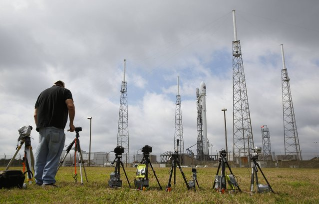 A photographer sets up a remote camera near the unmanned SpaceX Falcon 9 rocket, carrying NOAA's Deep Space Climate Observatory Satellite, at launch pad 40 at the Cape Canaveral Air Force Station in Cape Canaveral, Florida February 10, 2015. Space Exploration Technologies will try again Tuesday to launch the rocket with the U.S. satellite intended to watch for threatening solar storms, NASA said on Monday. (Photo by Scott Audette/Reuters)