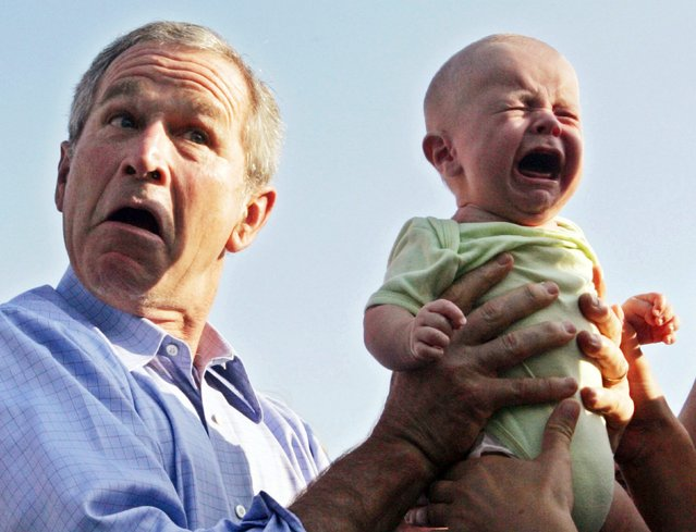 U.S. President George W. Bush hands back a crying baby that was handed to him from the crowd as he arrived for an outdoor dinner with German Chancellor Angela Merkel in Trinwillershagen, Germany in this July 13, 2006 file photo. (Photo by Jim Bourg/Reuters)