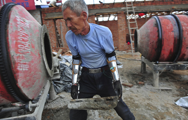 Sun Jifa moves a brick as he works to build his new house in Yong Ji county, Jilin province, September 25, 2012. Chinese farmer Sun, who lost his forearms in a dynamite fishing accident 32 years ago, could not afford to buy prosthesis. He spent two years guiding his two nephews to build him prosthesis from scrap metal, plastic and rubber. Over the years, Sun and his nephews have built about 300 prosthetic limbs for people in need, charging 3000 RMB ($476) each. (Photo by Sheng Li/Reuters)