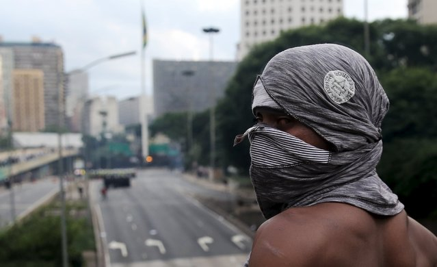 A demonstrator looks on in front of riot police (Rear) during a protest against fare hikes for city buses in Sao Paulo, Brazil, January 8, 2016. (Photo by Nacho Doce/Reuters)