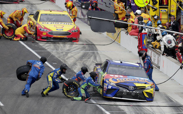 NASCAR Cup Series driver Kyle Busch (18) stops in front of driver Joey Logano (22) for tires and fuel on a pit stop during the NASCAR Brickyard 400 auto race at Indianapolis Motor Speedway, in Indianapolis Monday, September 10, 2018. (Photo by Michael Conroy/AP Photo)