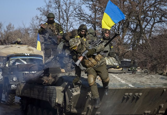 Members of the Ukrainian armed forces ride on an armoured personnel carrier (APC) near Debaltseve, eastern Ukraine, February 12, 2015. (Photo by Gleb Garanich/Reuters)