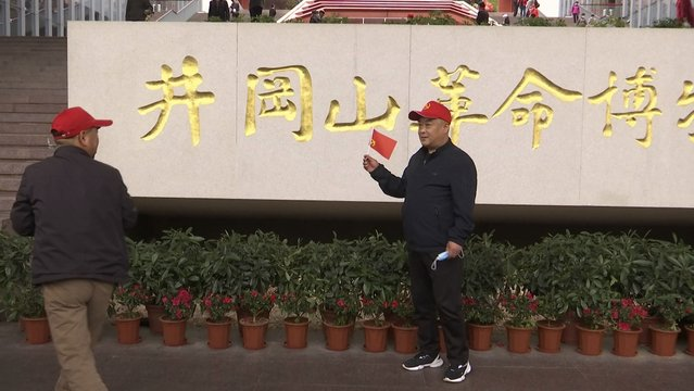 A tourists holds a flag as he poses for photographs in front of the sign for the Jinggangshan Revolution Museum in Jinggangshan in southeastern China's Jiangxi province, on April 8, 2021. On the hundredth anniversary of the Chinese Communist Party, tourists in China are flocking to historic sites and making pilgrimages to party landmarks. (Photo by Emily Wang/AP Photo)