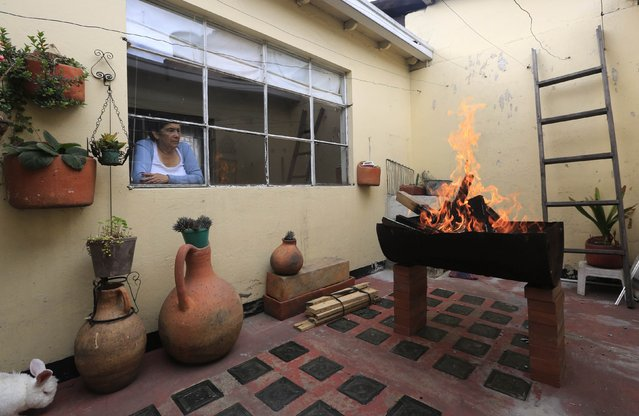 Rebeca Ruiz looks from her room window at a homemade grill fashioned out of an from an oil barrel in Bogota February 14, 2015. (Photo by Jose Miguel Gomez/Reuters)