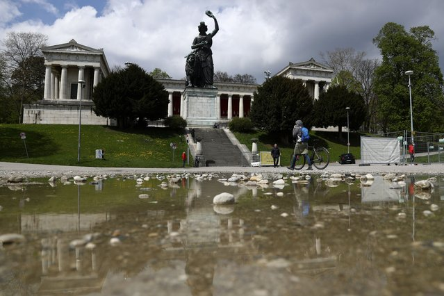 """People walk in the Theresienwiese' area where the """"Oktoberfest"""" beer festival is held, in front of the Bavaria statue, in Munich, Germany, Monday, May 3, 2021. The world's largest beer festival """"Oktoberfest"""" was cancelled last year due to the coronavirus outbreak. (Photo by Matthias Schrader/AP Photo)"""