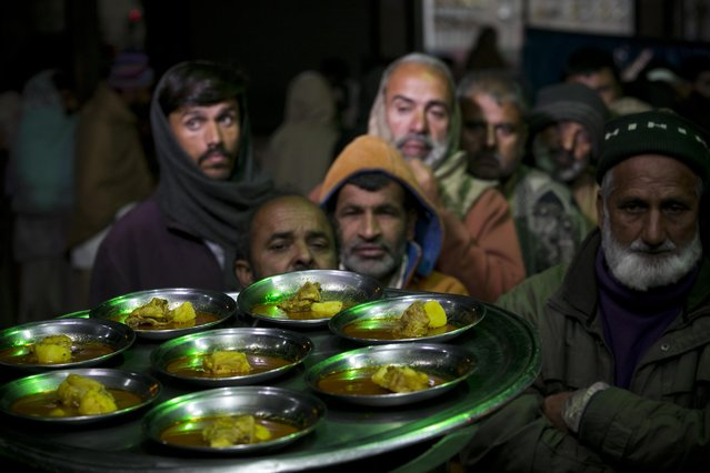 Poor people wait in a queue to receive a free meal in Rawalpindi, Pakistan, Wednesday, January 6, 2015. (Photo by B.K. Bangash/AP Photo)