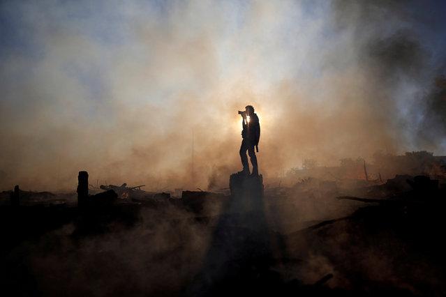 A photographer take a photos of a wildfire near the Paranoa neighbourhood in Brasilia, Brazil, July 20, 2018. (Photo by Ueslei Marcelino/Reuters)