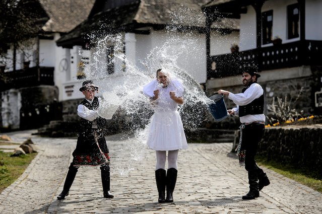 Dressed in folk costumes, young men pour water on young women in Holloko, a mountain village enlisted on the World Heritage List of Unesco, some 80 km northeast of Budapest, Hungary, 01 April 2021, during a press event. Holloko is famous for its traditional Easter celebrations but this year all the events have been cancelled due to the coronavirus. (Photo by Peter Komka/EPA/EFE)