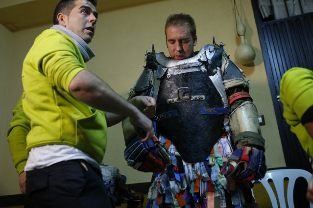 Armando Vicente, 30, right, is helped to put on his Jarramplas costume before he makes his way through the streets beating a drum during the Jarramplas festival in Piornal, Spain, Wednesday, January 20, 2016. (Photo by Francisco Seco/AP Photo)