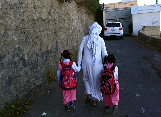 Saudi man Yazid al-Fefi holds the hands of his daughters as they arrive to their school after making their way through Fifa Mountain, in Jazan, south of Saudi Arabia, December 15, 2016. (Photo by Mohamed Al Hwaity/Reuters)