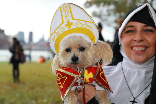 Susan from New York City holds her dog Tasha dressed a the the Pope during the 28th Annual Tompkins Square Halloween Dog Parade at East River Park Amphitheater in New York on October 28, 2018. (Photo by Gordon Donovan/Yahoo News)
