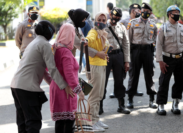Police search visitors entering the East Jakarta District Court where the sentencing hearing of firebrand cleric Rizieq Shihab is being held in Jakarta, Indonesia, Thursday, May 27, 2021. (Photo by Dita Alangkara/AP Photo)