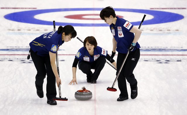 Japan's third Sayaka Yoshimura (C) directs her team-mates Anna Ohmiya (L) and Kaho Onodera as they sweep during their curling round robin game against Finland at the World Women's Curling Championship in Sapporo March 16, 2015. (Photo by Thomas Peter/Reuters)
